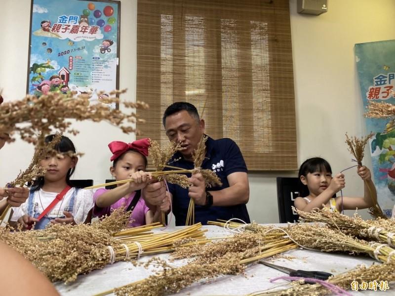 金門縣長楊鎮浯(右2)促銷7月登場的親子嘉年華,與小朋友學編高粱掃帚。(記者吳正庭攝)