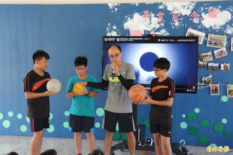 麥寮興華國小自然老師蔡宗達跟小朋友說明日環食發生現象。(記者黃淑莉攝)