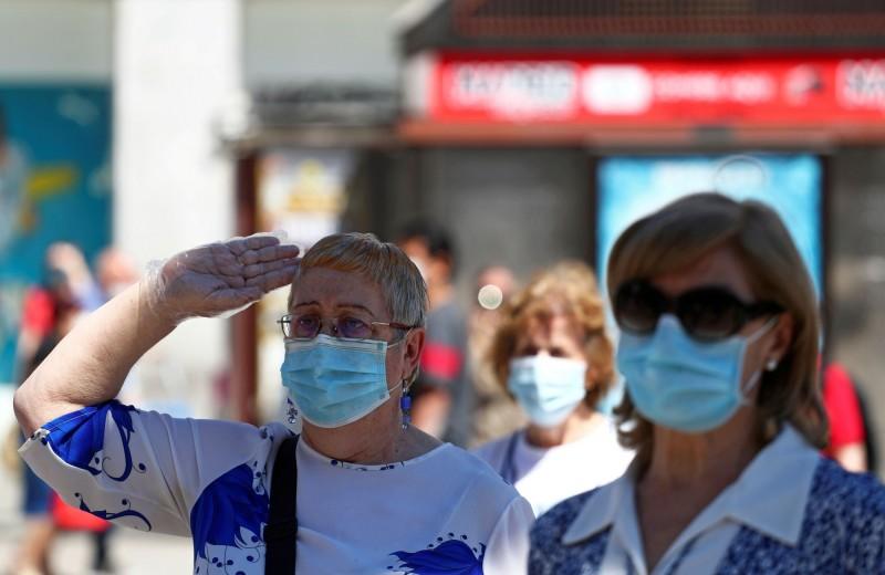 西班牙被質疑疫情數據「蓋牌」後,一舉新增1177例死亡。圖為西班牙民眾戴口罩防疫。(路透)