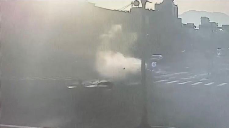 車禍瞬間揚起一陣白煙,騎士被撞飛。(記者洪臣宏翻攝)