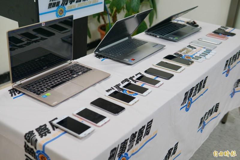 警方查扣贓證物手機64支、教戰手冊9份、金融卡及U盾6組、SIM卡3張、筆電7台等證物。(記者何宗翰攝)