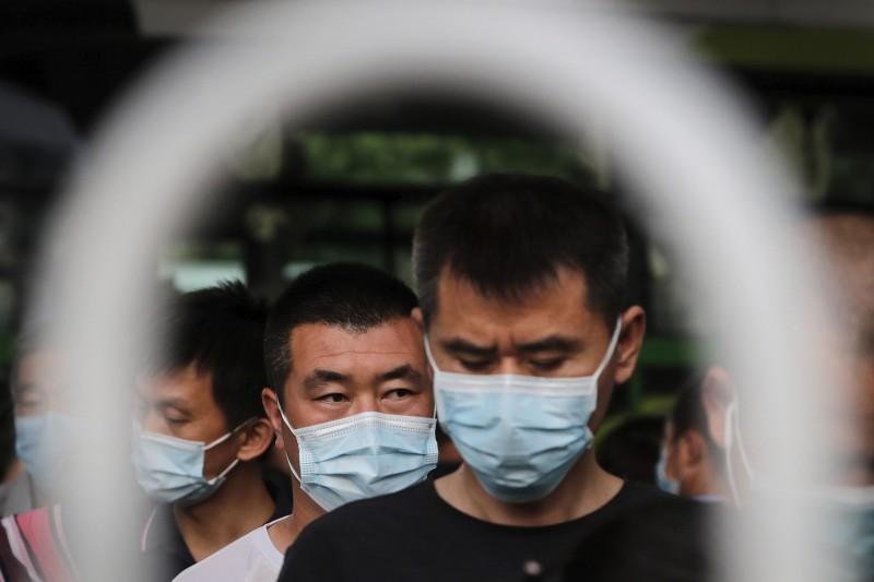 北京民眾戴上口罩準備搭公車。(美聯社)