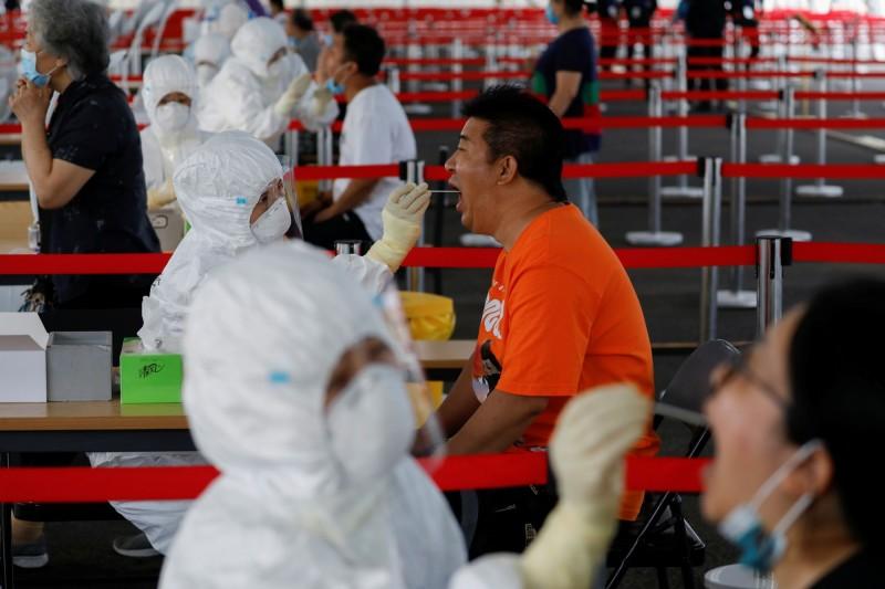 北京昨天再新增7例本土病例與1例無症狀感染者。圖為北京民眾接受武漢肺炎檢測。(路透)