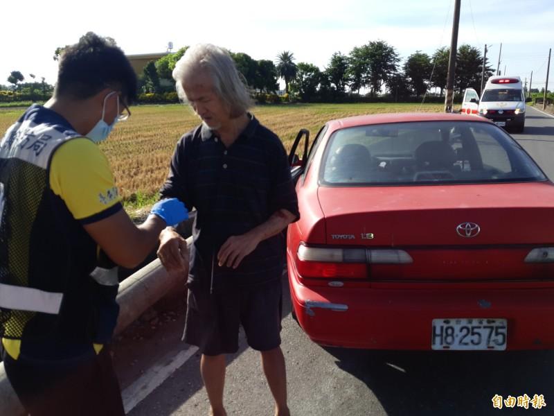 開車的黃姓老翁手部輕微擦傷由救護人員現場包紮。(記者黃明堂攝)