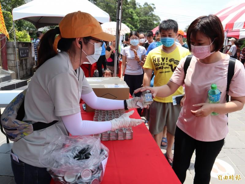 民眾排隊索取市府贈送具有「真有錢」意涵的限量金午吉午時水紀念瓶。(記者歐素美攝)