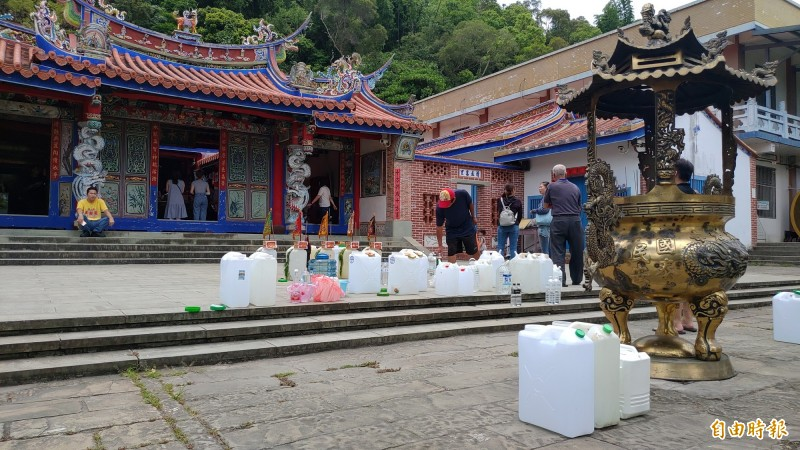 民眾取完午時水會在曝曬百年古廟清水岩寺前廣場15分鐘,吸收整年磁場最盛陽氣。(記者陳冠備攝)