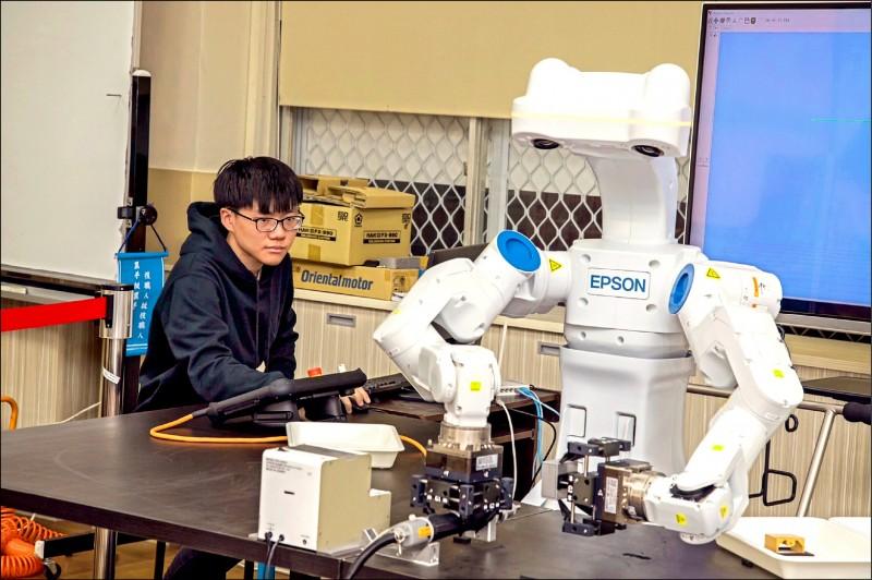 崑山科大學子實際操作智慧機器人機械手臂。(記者萬于甄翻攝)