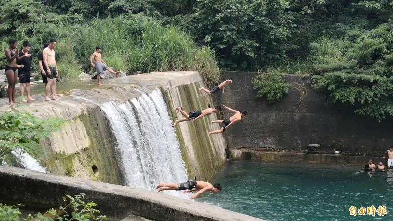 花蓮砂婆礑溪雖然前一天才有人因為跳水出意外,今天仍有大批民眾前往戲水,還有人不怕死地從高達3層樓的水泥壩體跳下去。(記者花孟璟攝)