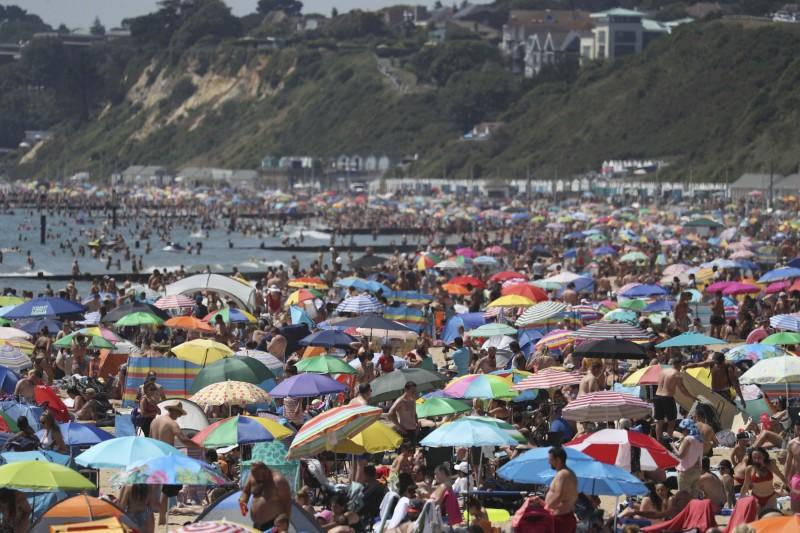 英國疫情未歇,南部海濱城市波茅斯卻因熱浪來襲湧入上萬遊客。英國政府警告,若民眾不遵守規定,迫不得已仍會下令海灘關閉。(美聯社)