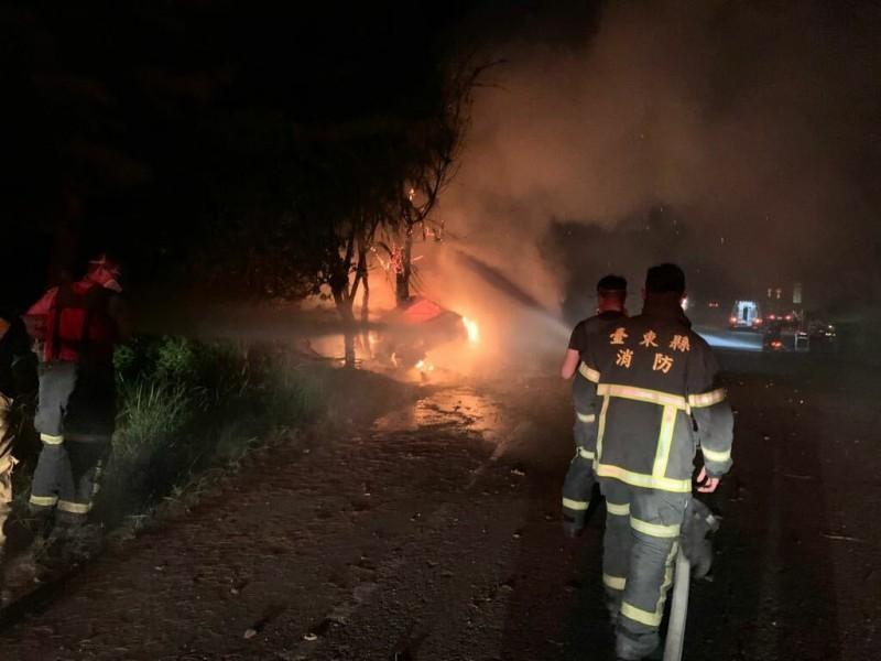一輛轎車27日深夜在台東市人工湖旁堤防道路自撞全面燃燒,消防人員拉水線滅火。(記者陳賢義翻攝)