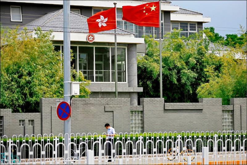 圖為香港特區政府駐北京辦事處外一景,中國國旗「五星旗」和特區旗「洋紫荊旗」飄揚。(路透檔案照)