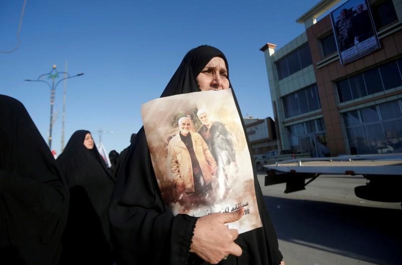 伊朗29日對美國總統川普發布逮捕令。圖為1名伊朗女子悲痛地拿著蘇萊曼尼的畫像。(路透檔案照)