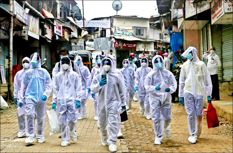 印度醫護人員穿著全套防護衣,二十八日前往孟買貧民窟的醫療營提供協助。(美聯社)