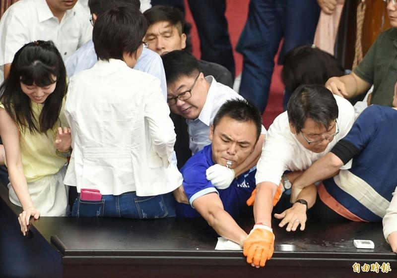國民黨立委以鐵鍊橫跨主席台堅守之下,民進黨立委雖有人數優勢,仍耗費約50分鐘才「奪回」主席台。(記者劉信德攝)