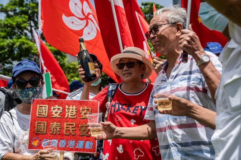 中國人大今日通過《港版國安法》,支持法案的香港人揮舞著中國和香港特別行政區的區旗慶祝。(彭博)