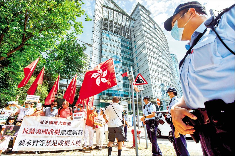 親中國的香港示威者六月三十日在中國外交部駐港特派員公署外,舉起香港區旗與「反美霸權大聯盟」標語,支持港版國安法,抗議美國對香港實施制裁。(彭博)