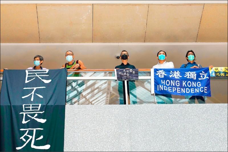 中國全國人大常委會表決通過香港國安法,香港民眾在中環一座商場舉著寫有「民不畏死」、「香港獨立」等標語的布條抗議。(美聯社)