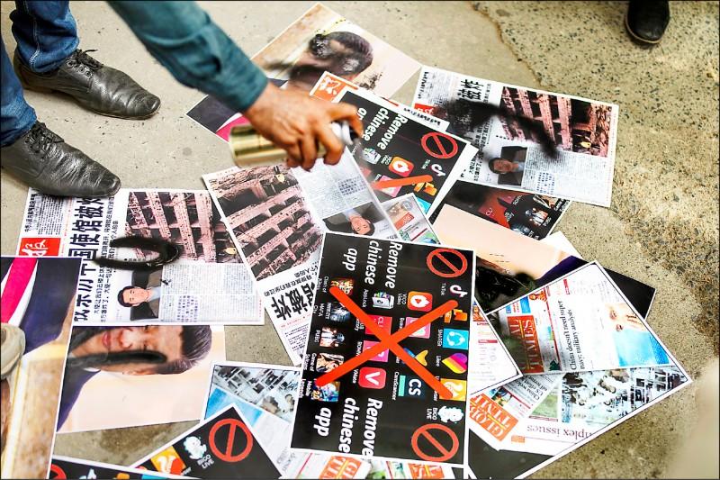 印度政府宣布,將禁用抖音、微信等五十九個中國手機應用程式。圖為新德里一名記者六月三十日在印有中國APP圖示的紙張上噴黑漆。(美聯社)