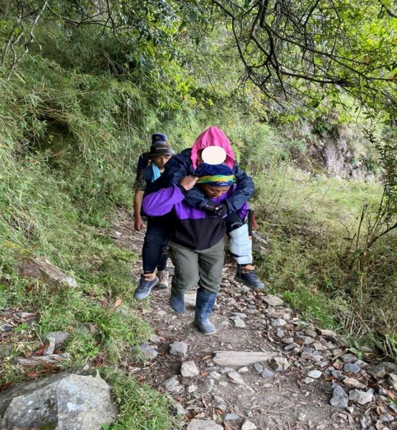 玉山單攻頻傳山難,有山友體力不支軟腳跌倒受傷,由救難人員協助揹下山就醫。(玉管處提供)