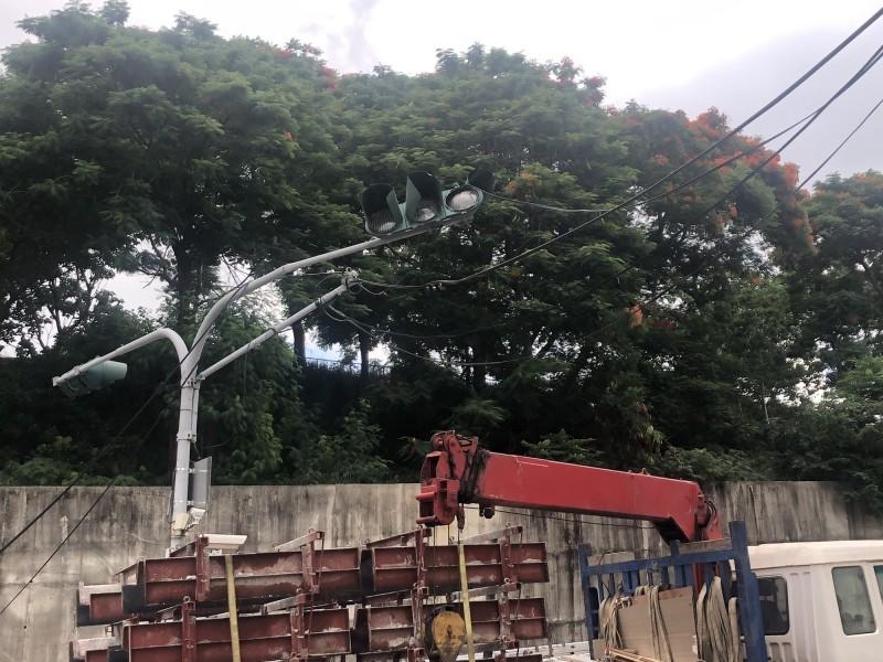 1輛工程車吊臂疑似忘了收起,勾到電線將交通號誌桿扯斷。(記者湯世名翻攝)