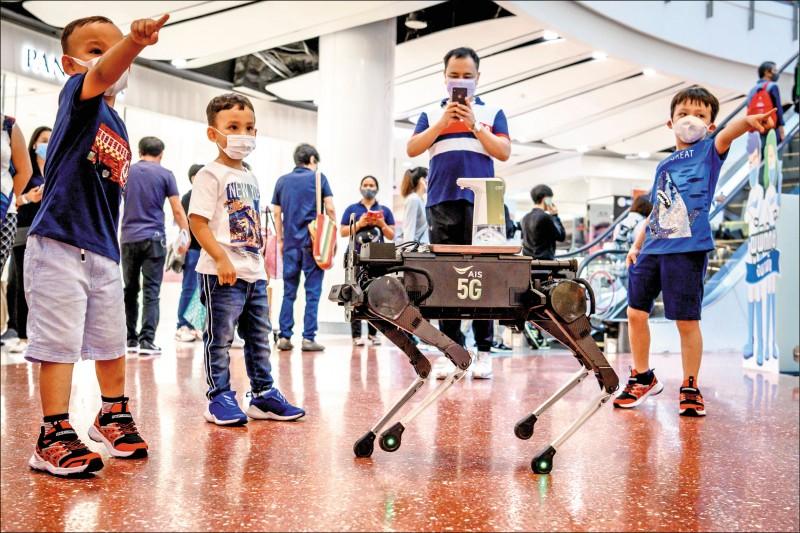 在曼谷一處商場內,孩童和防疫機器狗「K9」玩在一起。(法新社檔案照)