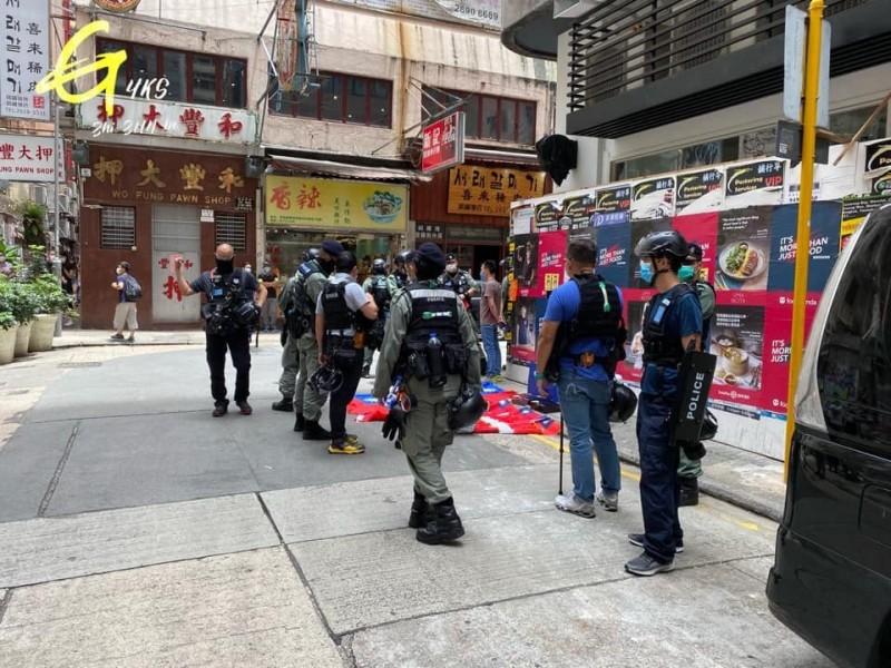 香港攝影師發現,港警包圍1名男子,並起出多面台灣國旗。(YKS至尊寶授權使用)