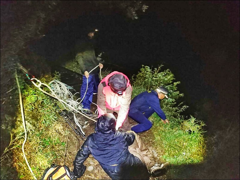 玉山單攻頻傳山難,有山友(圖下)摸黑下山不慎墜崖,幸好卡在邊坡,由救難人員以繩索救回步道。(玉管處提供)