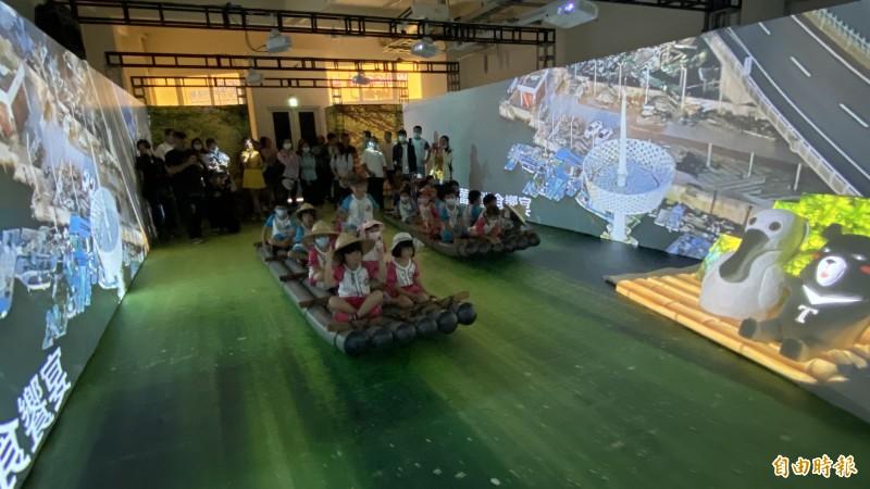 遊客坐在膠筏上欣賞光雕。(記者楊金城攝)