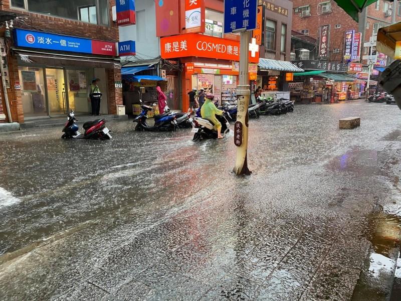 淡水老街(中正路)積水漫淹到人行道上。(楊云萱提供)