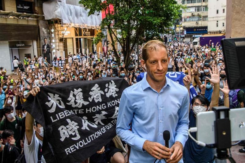 7月1日香港街頭示威抗議時,有人展示寫有「光復香港 時代革命」的黑底白字布條。(法新社)