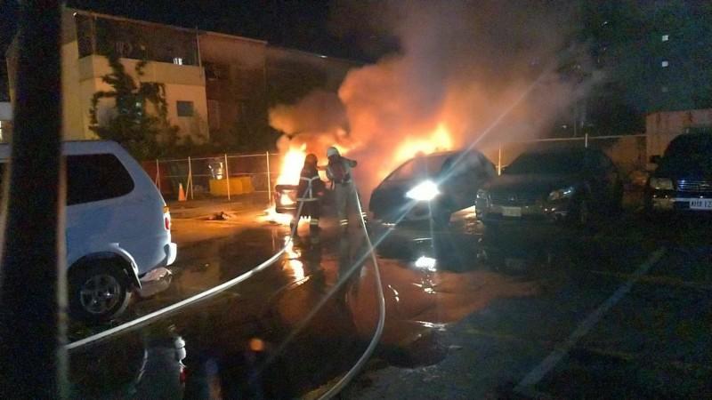 消防人員全力灌救失火的兩輛小客車。(記者王俊忠翻攝)