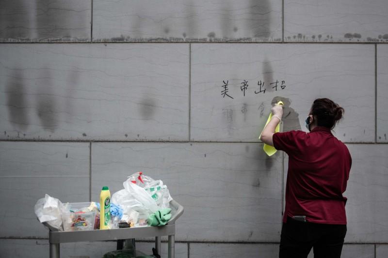 中國「港版國安法」通過實施,許多網友開始清理社群平台發文紀錄、改掉用戶名稱,甚至關閉帳號。圖為香港清潔人員清除牆上的抗議標語。(彭博)