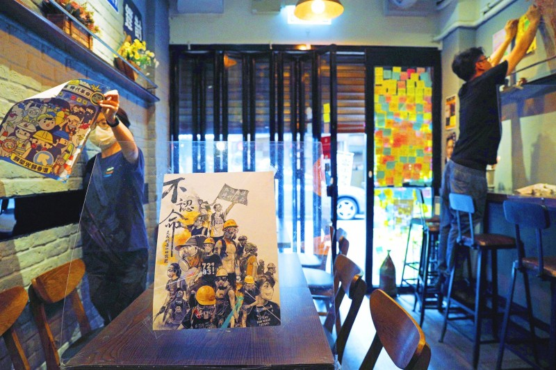 Restaurant employees yesterday remove stickers and posters with messages supporting the pro-democracy movement in Hong Kong, in the wake of China's National People's Congress Standing Committee passing new national security legislation for the territory.   Photo: AP