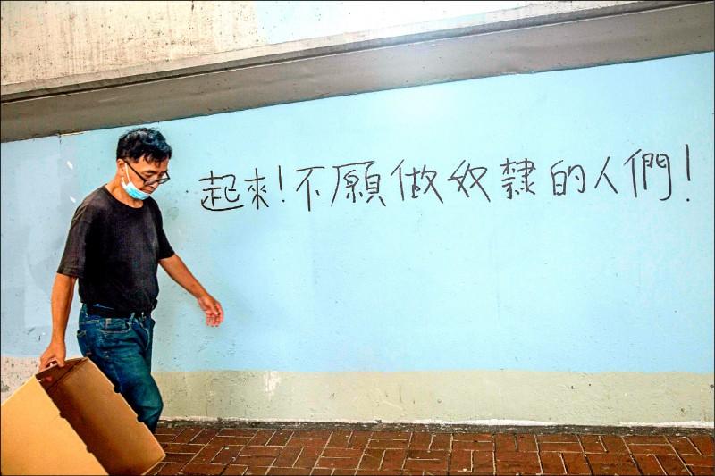 一名男子三日走過塗寫中國國歌義勇軍進行曲歌詞「起來!不願做奴隸的人們」的牆壁,港人藉此呼籲更多人起身反抗北京政府。(法新社)