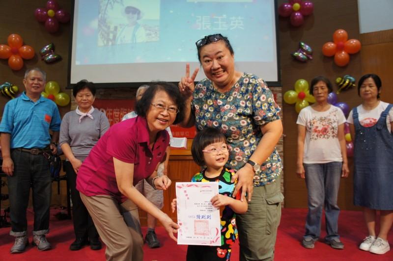 高雄市社會局代理局長謝琍琍(左,紅衣),頒獎表揚13名臨時短期照顧員。(社會局提供)