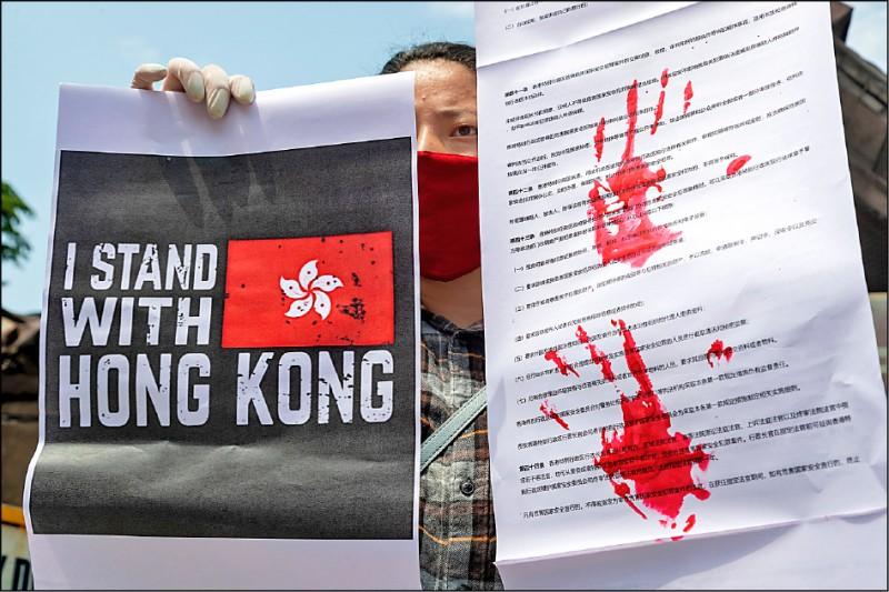 一名西藏流亡人士四日在印度達蘭薩拉(Dharamsala)持染上血手印的港區國安法條文影本,以及寫有「我與香港同在」的標語,聲援同受中共打壓的香港人。(美聯社)