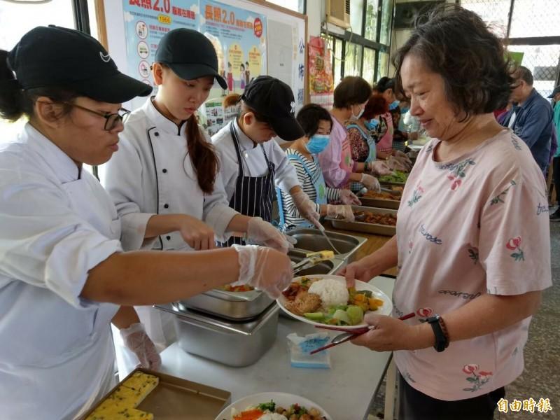新竹市政府社會處全國首創幸福小蜜蜂移動餐車開進沒有共餐的社區,以現煮方式提供長輩用餐服務,且還有用餐隔板隔著,讓長輩們開心笑了。(記者洪美秀攝)