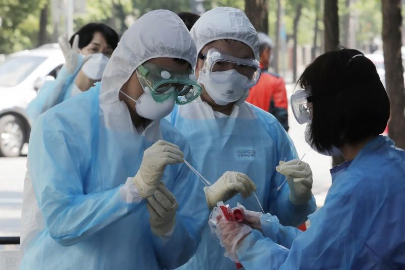 南韓防疫單位最新統計,4日單日新增61例確診。圖為首爾醫事人員採集檢體情況。(美聯社)