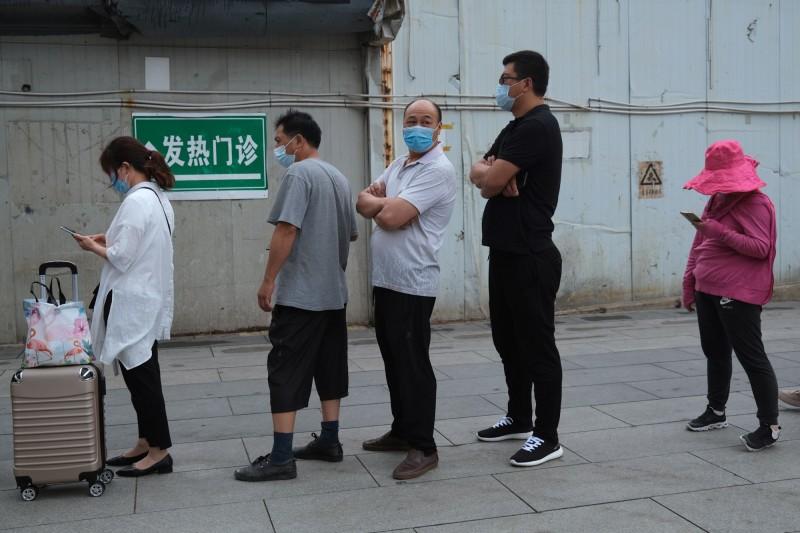 北京昨單日新增2例確診,為連續第7日呈個位數。圖為北京民眾排隊接受核酸檢測情況。(路透)