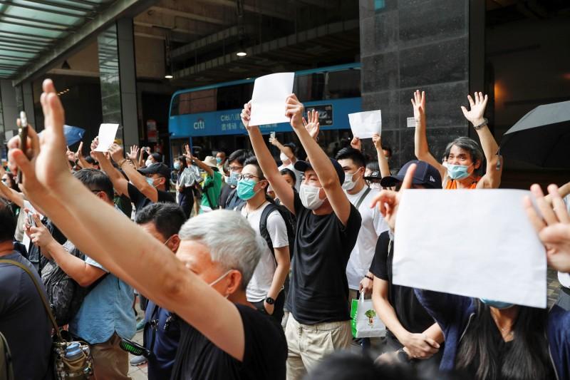 「高舉白紙的少女」引起社會熱議後,港人紛紛效仿該作法。近來有港人發起「白紙抗爭」運動,定於明日傍晚6點於香港觀塘舉行,屆時集會上眾人將高舉白紙,並以靜默的方式「抗議」。圖為港人3日聚集在香港東區法院外高舉白紙,聲援七一遊行上因持有反送中標語而遭港警拘捕的港人。(路透)