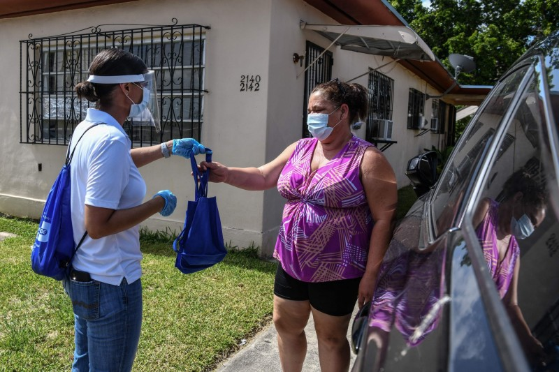 美國佛羅里達州與德州淪為美國國內最新疫情重災區。圖為佛羅里達州民眾分發消毒劑。(法新社檔案照)