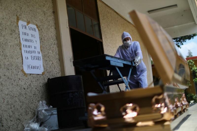 墨西哥因武漢肺炎死亡人數正式突破3萬。圖中,一名墨國葬儀社員工正在將武漢肺炎死者遺體移至棺材內。(路透)