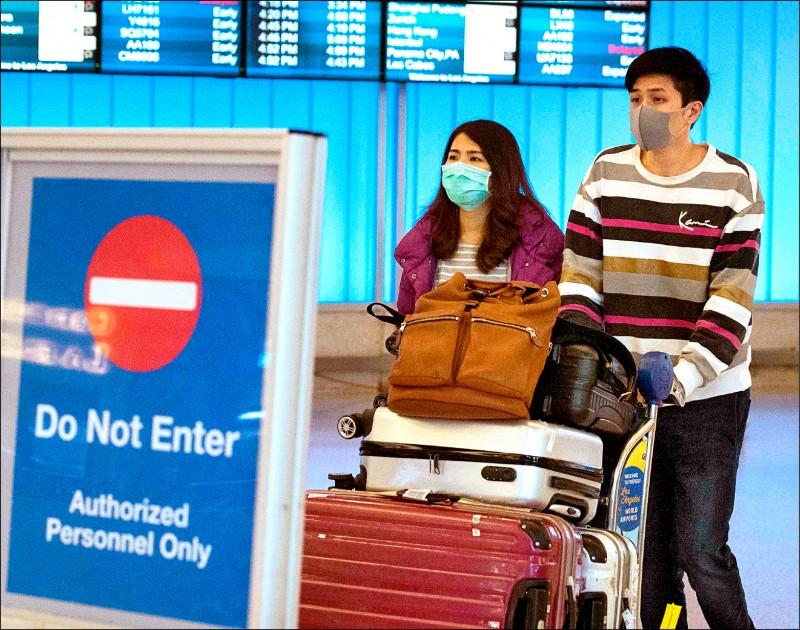美國二月初起,禁止有中國旅遊史的外籍人士入境,但香港和澳門除外。圖為疑似中國旅客一月間戴著口罩抵達美國洛杉磯國際機場。 (法新社檔案照)