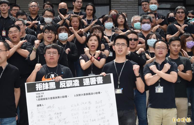 國民黨立委助理約百人6日著黑衣在立法院議場前舉行記者會,抗議綠委誣指藍委助理是黑衣人活動,並簽署「拒抹黑 反霸凌」連署書,要求綠委道歉。(記者廖振輝攝)