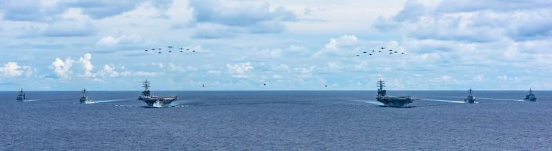 美國海軍尼米茲號航艦戰鬥群與雷根號航艦戰鬥群進軍南海,7月4日起,進行大規模演習,美軍今天公布兩艘航艦並肩航行,伴隨打擊群艦艇與各自空中機隊的畫面,相當震撼。(圖擷取自美軍第七艦隊官網)