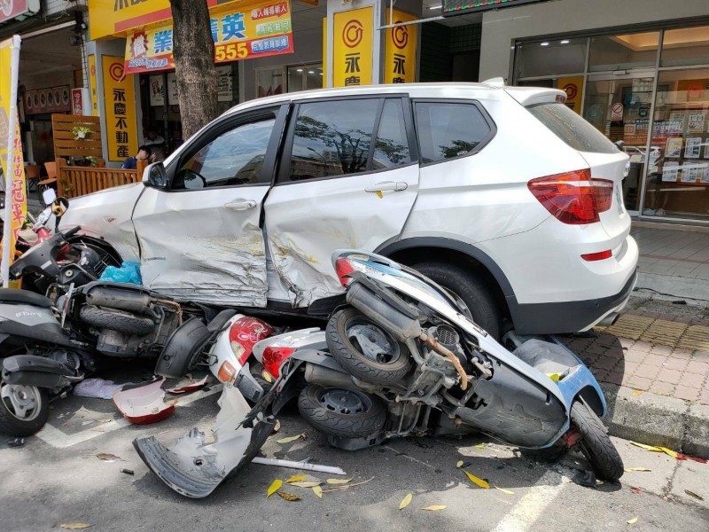 林女駕BMW休旅車連撞2車,再刷一整排18部機車,造成4人受傷。(記者陳文嬋翻攝)
