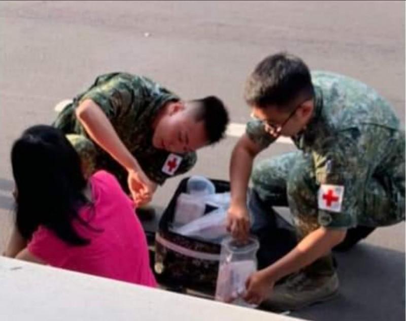 路過的陸軍234旅上士鄭馴樺(左)、下士張家維(右)熱心幫遭撞傷的女騎士包紮,獲網友讚揚。 (記者陳建志擷取自臉書「大里人聊天室」)