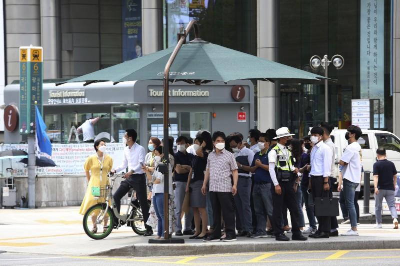 南韓首都圈仍面臨疫情壓力,圖為首爾街頭,可見到行人多配戴口罩自保。(美聯社)