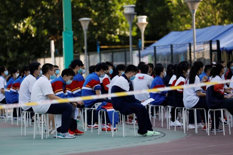 中國高考今日登場,圖為北京某考場學生在外等候考試情況。(路透)