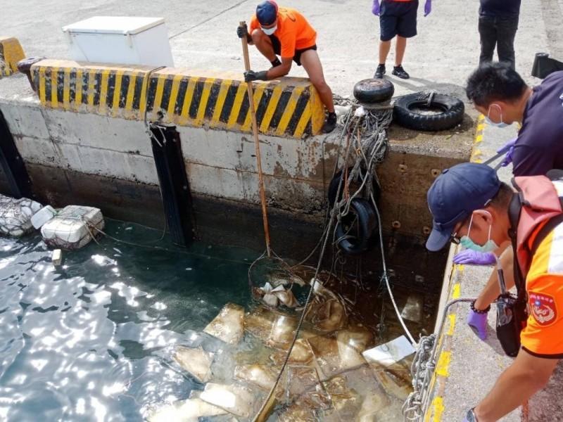 安檢弟兄與農漁局及環保局人員,共同以吸油棉清除海面油污。(第七岸巡隊提供)